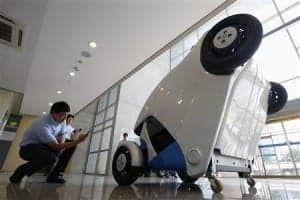 A visitor photographs Armadillo-T, a foldable electric vehicle, at Korea Advanced Institute of Science and Technology in Daejeon